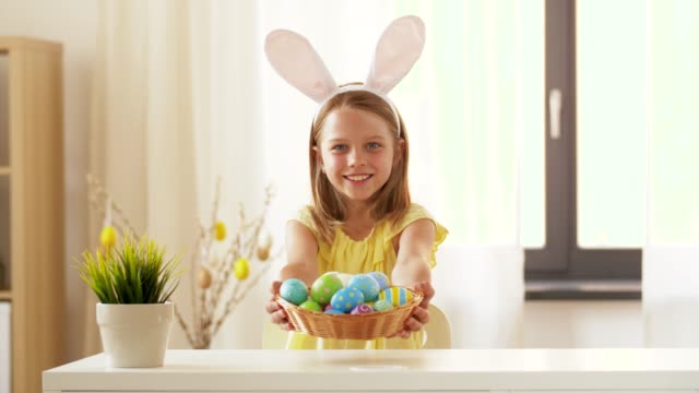 happy girl showing colored easter egg at home