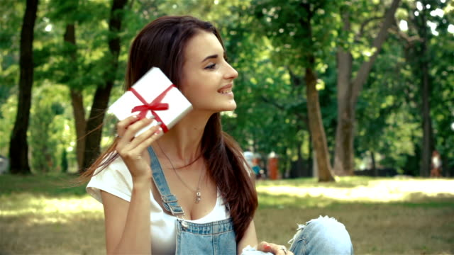 happy girl sits in the Park on the grass and holding gift box video