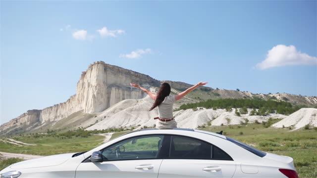 happy girl sitting on roof of her car, relaxing and enjoying road trip - wschodnio europejski filmów i materiałów b-roll