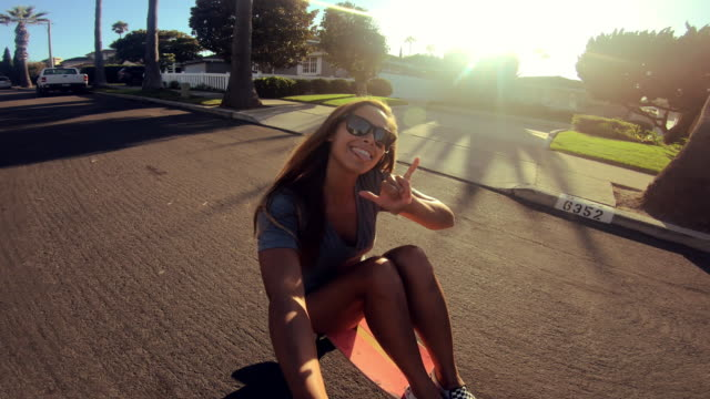 POV happy girl skateboarding down street at sunset holding selfie camera Point of view selfie shot of girl riding skateboard down palm tree lined street at sunset skating stock videos & royalty-free footage