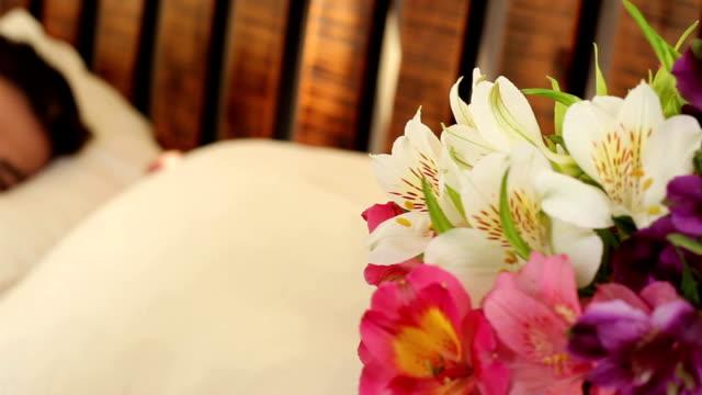 happy girl smelling flowers while her boyfriend sleeps in bed - blomsterarrangemang bildbanksvideor och videomaterial från bakom kulisserna