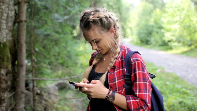 Happy girl standing in the forest and texting sms on smartphone video