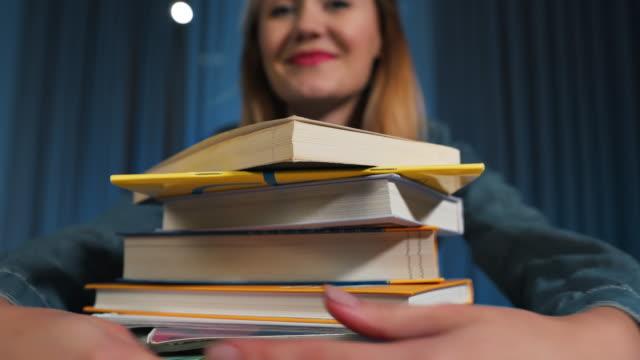 mutlu kız öğrenci bir kot gömlek mutlu bir büyük kitap yığın sarılmak. yakın çekim - çalışma kitabı stok videoları ve detay görüntü çekimi