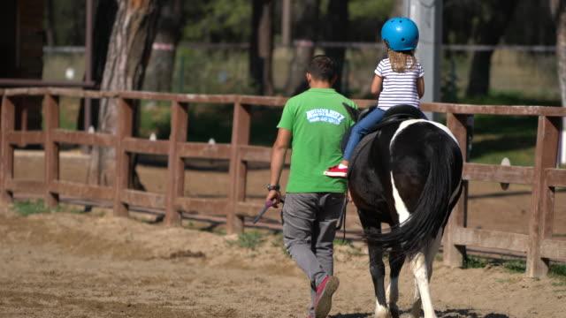 乗馬レッスンを取って幸せな女の子 - 動物に乗る点の映像素材/bロール