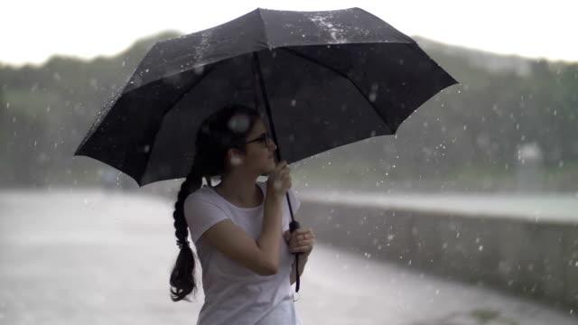 vídeos de stock e filmes b-roll de happy girl under the umbrella enjoying in the rain, heavy rain, slow motion, outdoors - chapéu