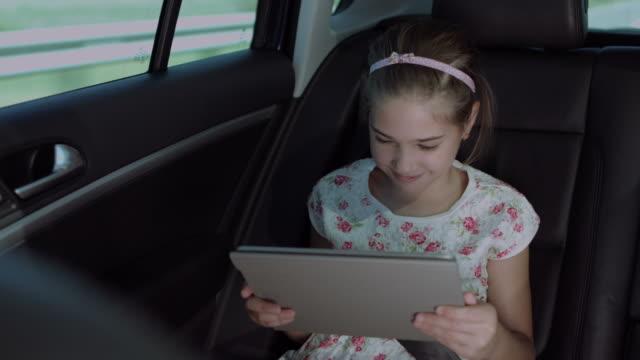 glad flicka titta på tecknade serier på surfplattan i bilen - konstkultur och underhållning bildbanksvideor och videomaterial från bakom kulisserna