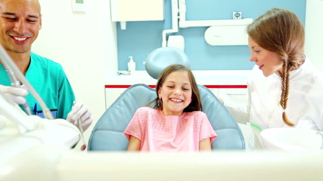 Happy girl with dentist and surgeon giving thumbs up after dental check up ビデオ