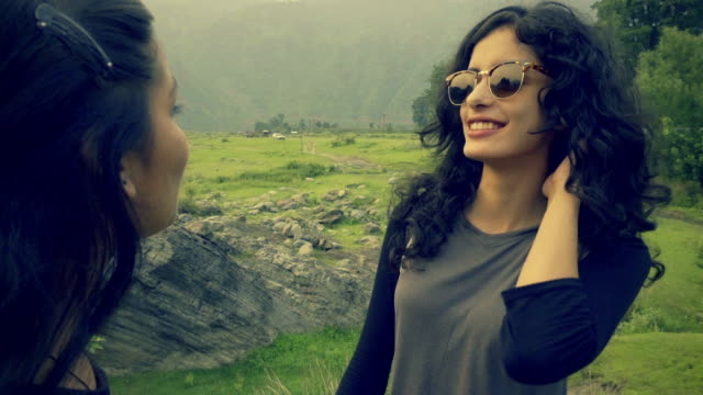 Happy girl with her female friend enjoying vacation in hills. video