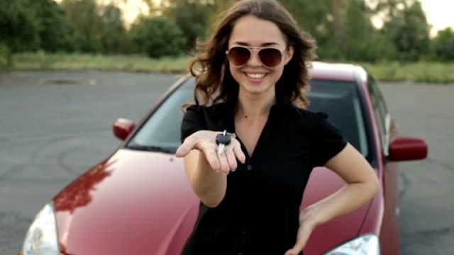 happy girl with key in hand from new car - kupować filmów i materiałów b-roll