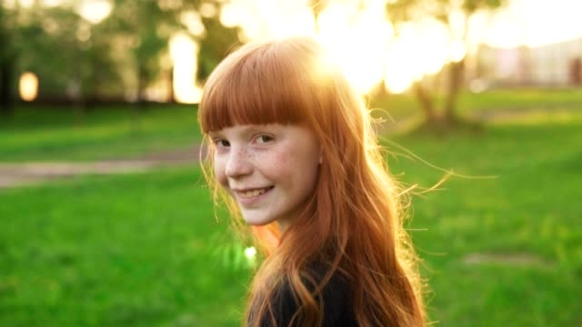Happy girl with red hair walking, looking into camera and smiling at sunset