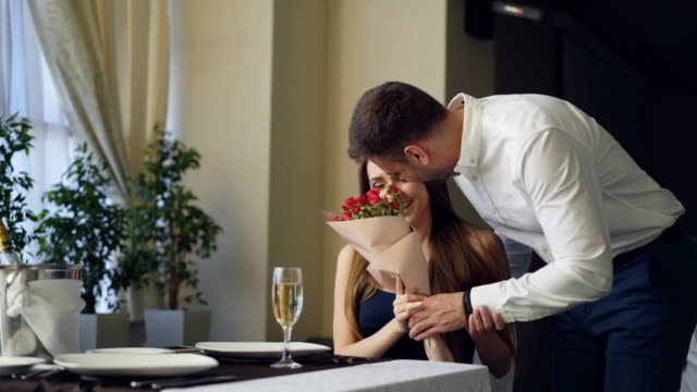 Happy girlfriend is getting flowers and present from her boyfriend after waiting for him alone in restaurant. Romantic relationship, gifts and fine dining concept.