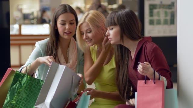 glada väninnor på shopping diskutera nya inköp i paket från dyra butiker i säsongen av försäljning och rabatter - köpnarkoman bildbanksvideor och videomaterial från bakom kulisserna
