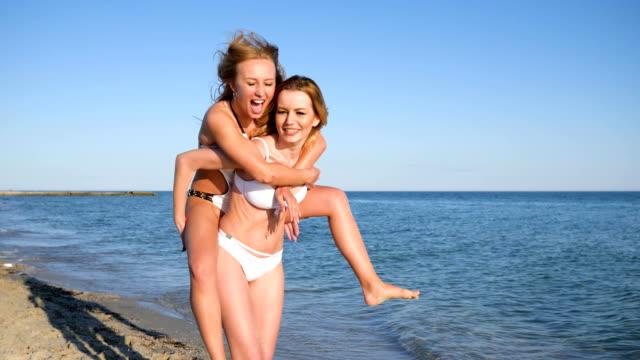 vidéos et rushes de heureux copines faire couler l'eau de mer, jeune fille saute sur le dos d'un ami, lent - joggeuse