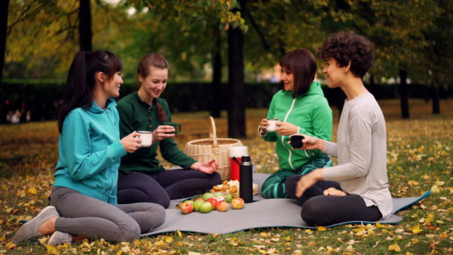 happy girls are having picnic in park sitting on yoga mats and eating after outdoor practice in autumn, girls are talking and laughing. communication and food concept. - odzież sportowa filmów i materiałów b-roll