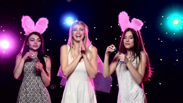 Happy girls at bachelorette party blowing soap bubbles. Slow motion