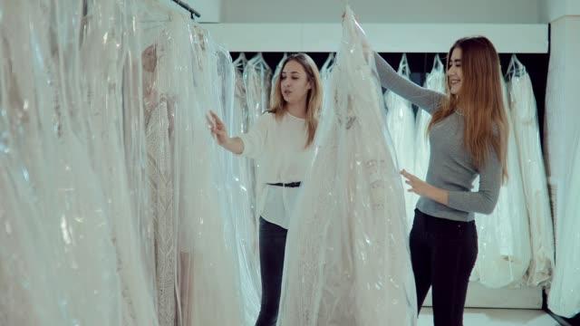 glada tjejer titta på bröllopsklänningar i salongen. vacker brud med en flickvän välja vackra kläder. flickor ler. bröllop preparat. - aftonklänning bildbanksvideor och videomaterial från bakom kulisserna