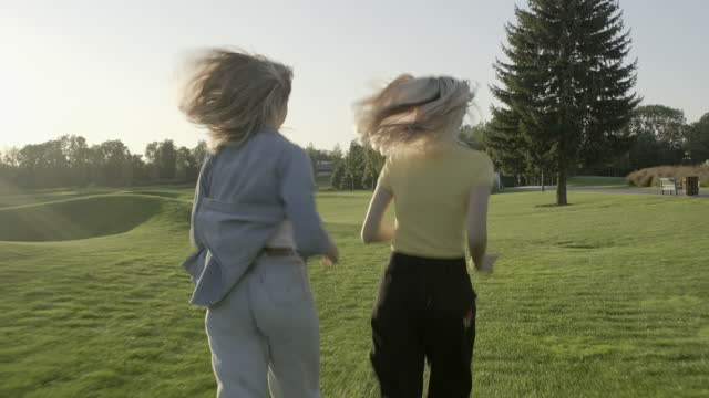 Happy girls running on grass, green lawn, sunset landscape summer park background, back view, slow motion