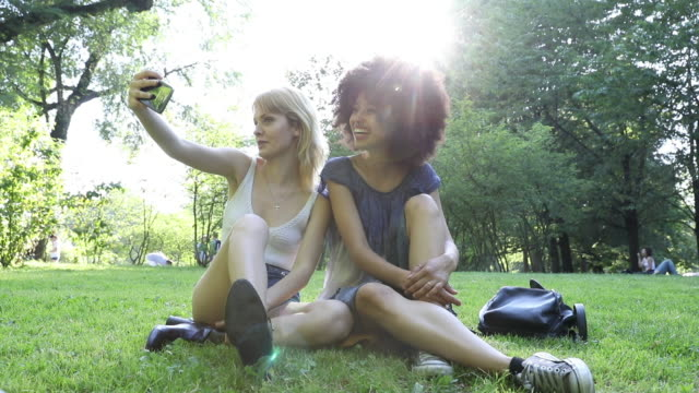 Happy girls taking a selfie at the park - video
