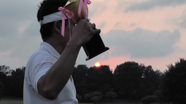Happy golfer holding driver and trophy while raising his arms with sunset background.Success concept.Sports Cinemagraphs
