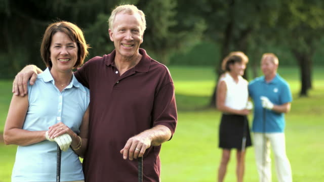Happy golfing couple looks at the camera while others talk.  baby boomers stock videos & royalty-free footage