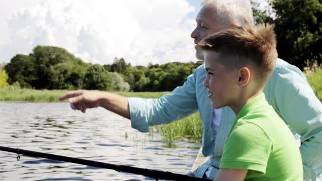幸せな祖父と孫の川バースに釣竿と - 漁師 外人点の映像素材/bロール