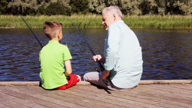 vídeos de stock e filmes b-roll de happy grandfather and grandson with fishing rods on river berth - fishman