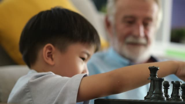 vídeos de stock e filmes b-roll de happy grandfather having a great time with his grandson - xadrez