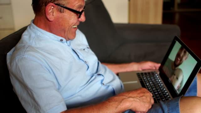 froh, dass großvater seinem enkel sieht zum ersten mal über das internet. drei generationen von männern, eine glückliche familie. ein reifer mann im gespräch mit seinem sohn und enkel auf skype - großeltern stock-videos und b-roll-filmmaterial