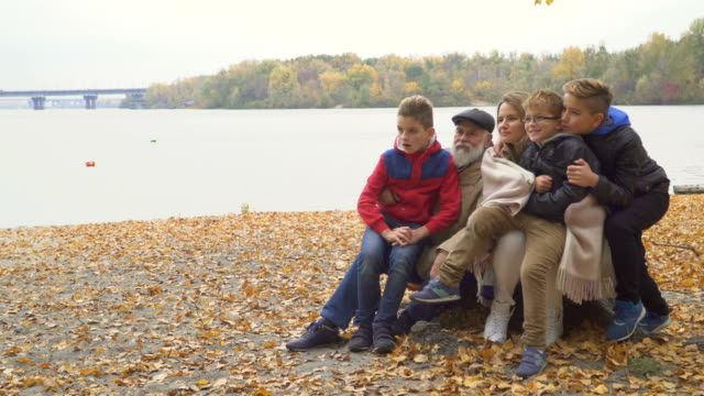 Happy grandfather with adult daughter and grandchildren in autumn park video