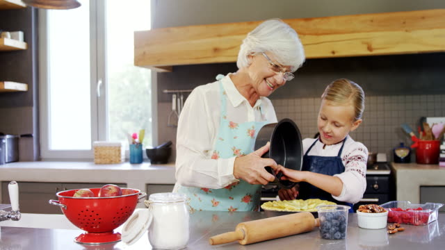 happy grandmother and granddaughter preparing pie 4k - kitchen room video stock e b–roll