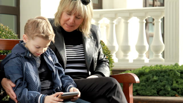 Happy grandmother and grandson playing together on mobile phone video