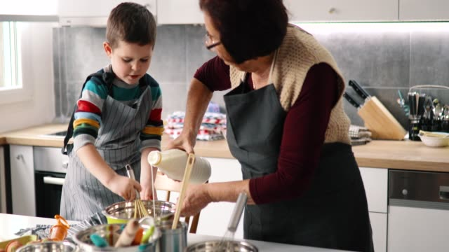 Happy grandmother and grandson preparing cookies Happy grandmother and grandson preparing cookies mixing bowl stock videos & royalty-free footage