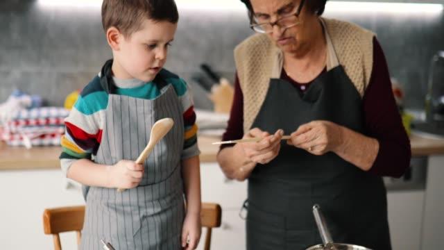 Happy grandmother and grandson preparing cookies