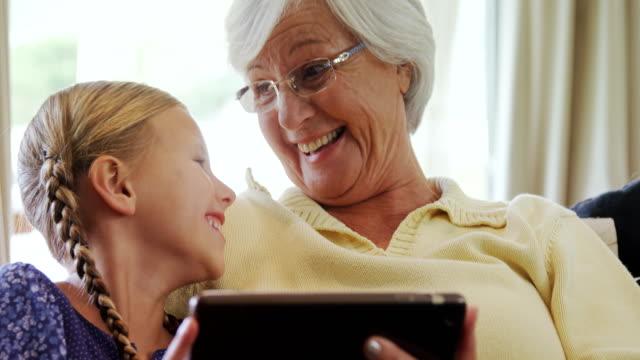 Avó feliz e menina sentado no sofá e usando tablet 4K 4K - vídeo