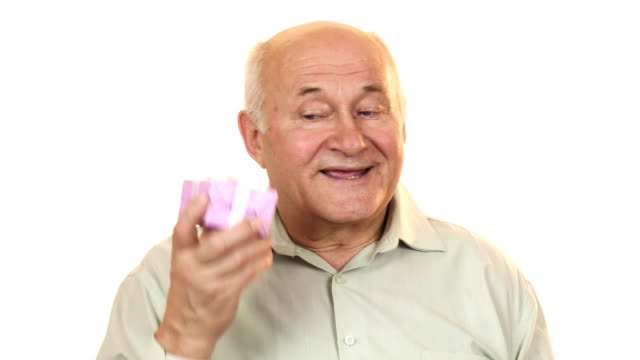 Happy grandpa smiling listening to a gift box guessing what is inside video