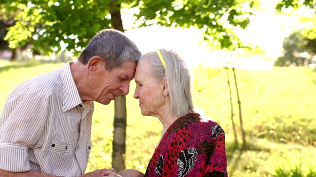 Happy grandparents touched foreheads in the Park. video