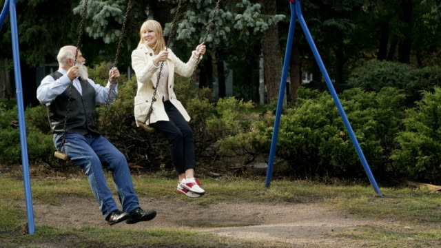 Happy gray-haired man with adult daughter swings on teeterboard video