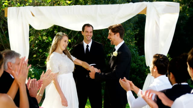 Happy groom showing off wedding ring and happily kissing, hugging bride 4K 4k video