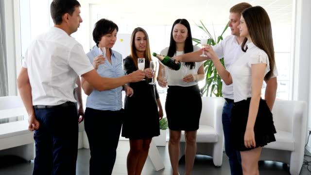 vidéos et rushes de joyeux groupe de collaborateurs, soulevant des toasts avec de l'alcool dans le bureau moderne - flûte à champagne