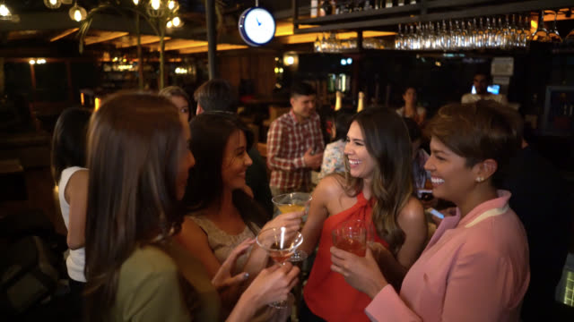 Happy group of female friends having fun at a bar gossiping and drinking cocktails video