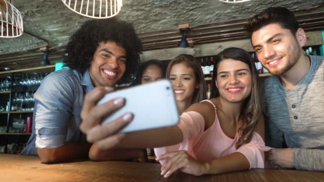 glada grupp vänner på en bar att ta en selfie med en smartphone leende - rörlig aktivitet bildbanksvideor och videomaterial från bakom kulisserna