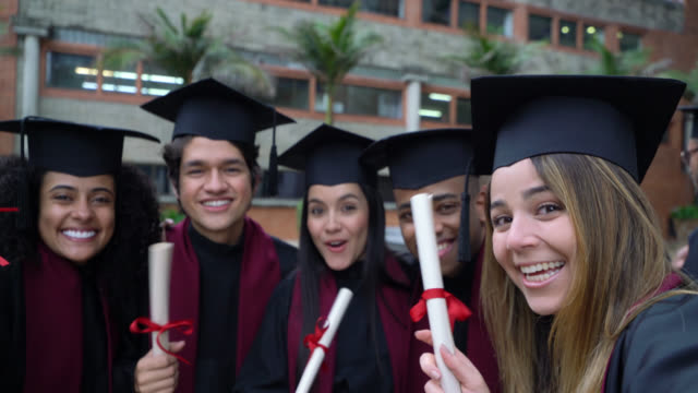 Happy group of friends on a video call with someone after their graduation ceremony from college Happy group of friends on a video call with someone after their graduation ceremony from college talking and smiling diploma stock videos & royalty-free footage