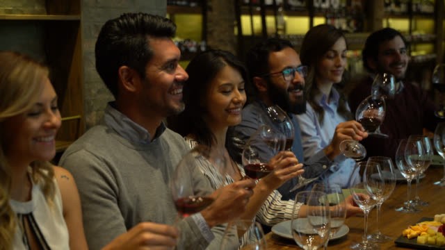 Happy group of Latin American people tasting wine at a cellar smiling