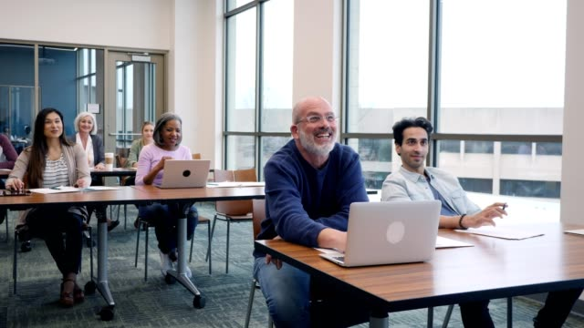 Happy group of mixed age, multi-ethnic college students attending class Group of diverse male and female college students listen to female professor give a lecture. A mature man talks to the teacher as he and the class share a laugh with the professor. adult stock videos & royalty-free footage