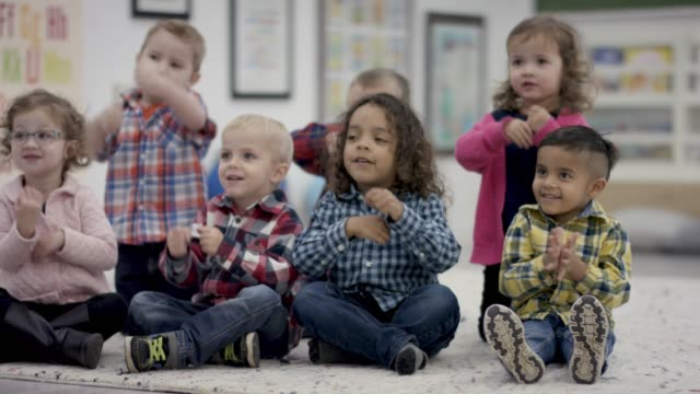 happy group of pre-school students sitting in class - kindergarten стоковые видео и кадры b-roll