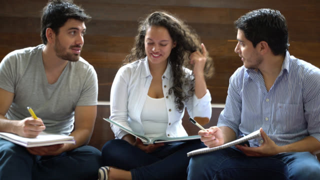 happy group of students sitting down studying and talking - esame università video stock e b–roll