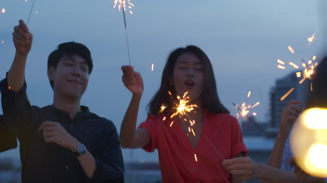 happy group of young friends enjoy and play sparkler at roof top party at evening sunset. holiday celebration festive party. teenage lifestyle party. slow motion. - cultura tailandese video stock e b–roll