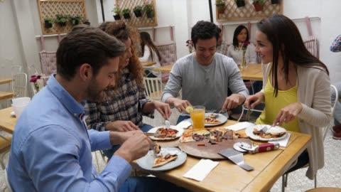 gruppo felice di giovani amici che condividono una pizza che parlano e si divertono mentre mangiano - abbigliamento casual video stock e b–roll