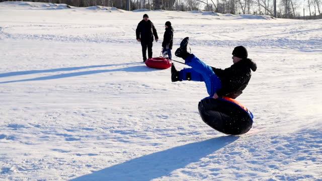 vídeos de stock, filmes e b-roll de passeios de cara feliz e sorrindo para snowtube colina coberta de neve e caindo - tubo objeto manufaturado