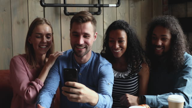 Happy guys showing funny photo editing application to friends.